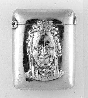 """Rectangle with blunt corners.  Plain silver surface with relief decoration in center a bust of grinning actor dressed as """"Charlie's Aunt""""."""