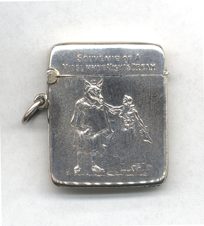 """Small, rectangular, featuring raised decoration of man on left, in donkey's head and toga-like costume, on right, reaching out towards him, is woman in long dress, inscribed above """"Souvenir of a Midsummer Nights's Dream""""; reverse inscribed """"Adelphi Theatre, 1906,  """"With Otho Stuart's Compliments."""" Thumb catch at front of lid, lid hinged on opposite side. Link attached below hinge. Striker in recessed groove on bottom."""