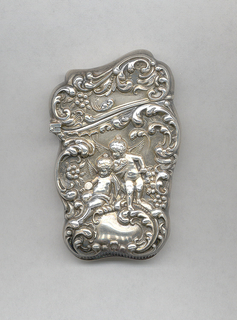 """Oblong, rounded sides and corners with irregular curves and counter-curves along four sides, upper portion of box wider than lower, with lid slanted on the diagonal; box features neo-rococo, repoussé decoration with c-scrolls, flowers and two cupids above a cartouche; reverse features no decoration except an irregularly shaped reserve inscribed """"Beth to Ceph, Xmas '96""""; reverse side also concave in form. Lid hinged on side. Slightly concave striker on bottom."""