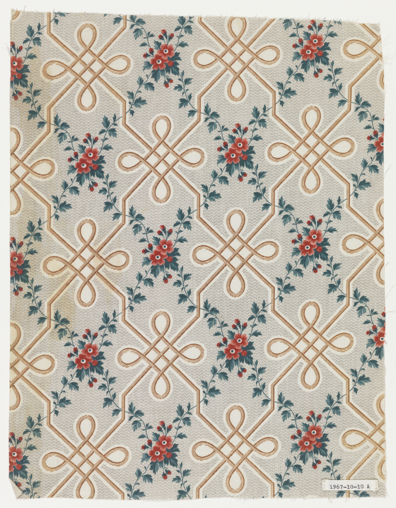 """Fragment of glazed, printed cotton. The ground is printed by """"molette"""" in minute grey zig-zag, leaving white areas, where an interlace design is printed in brown. Strawberry vines with clusters of little red flowers and green foliage form a diamond trellis."""