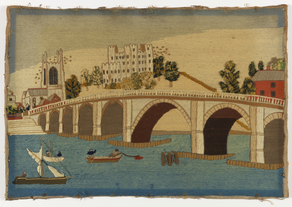 Bridge spanning a river; men in boats in the foreground and buildings across the bridge in the background.