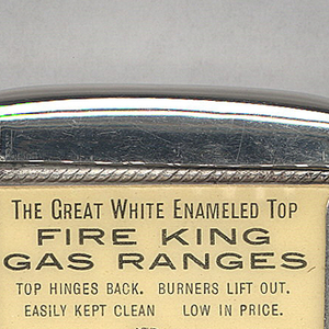 """Rectangular, curved top and bottom, featuring black printed decoration of female in blouse, tie, long skirt, and upswept hair cleaning beneath range top, inscribed above """"The Great  White Enameled Top. Fire King Gas Ranges. Top Hinges Back. Burners Lift Out. Easily Kept Clean. Low in Price."""" Inscribed below """"Manufactured By A. Weiskittel & Son, Baltimore, MD., U.S.A."""" Reverse features hot plate, inscribed above """"A Match Is All The Kindling Required Where Fire King Gas Stoves And Ranges Are Used."""" Inscribed below """"New Fire King Hot Plate With Hinged Top Gratings And Removable Drilled Burners."""" Inscribed in fine print below """"The Whitehead & Hoag Co., Newark, N.J."""" Lid hinged on side. Striker on bottom."""