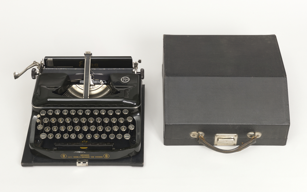 Typewriter (a) in black metal housing on flat base. Open keyboard and mechanics; black ribbon. White plastic keys with metal rims. Black leather-covered lid (b) with handle at front.