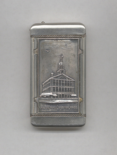 """Rectangular, curved corners, featuring raised decoration of 3/4 view of 3-storied building, with consecutive arched windows, pediment, and spire, inscribed """"Faneuil Hall, Boston, Mass."""", reverse features obelisk, inscribed """"Bunker Hill Monument, Boston, Mass."""" Both front and reverse decoration on metal panels that may be removed or exchanged. Lid hinged on side. Striker on bottom."""