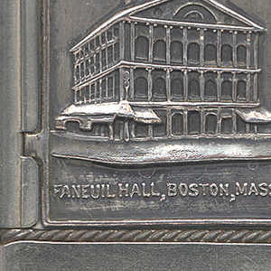 "Rectangular, curved corners, featuring raised decoration of 3/4 view of 3-storied building, with consecutive arched windows, pediment, and spire, inscribed ""Faneuil Hall, Boston, Mass."", reverse features obelisk, inscribed ""Bunker Hill Monument, Boston, Mass."" Both front and reverse decoration on metal panels that may be removed or exchanged. Lid hinged on side. Striker on bottom."