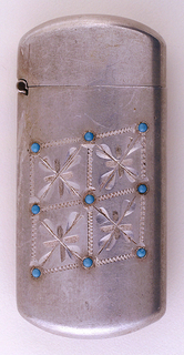 """Oblong, rounded top and bottom, featuring four etched frames containing flower motifs, all in grid pattern and turned slightly on the diagonal, each corner of frame puncuated with turquoise colored glass bead, total of nine in all. Reverse inscribed """"O.R., Sept. 21st. 98."""" Lid hinged on side. Striker on bottom."""