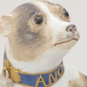 """Figure of a brown-spotted pug with cropped ears and a long tail.  Blue collar banded and inscribed in gold """"ANO 1741.""""  Collar secured by padlock."""