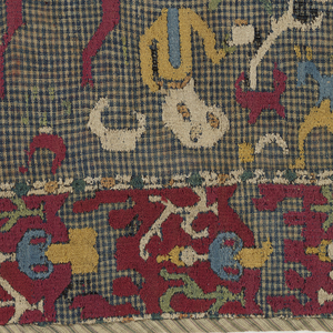 Cover of blue and white checked cotton cloth embroidered in colored silks. The design shows a man on horseback surrounded by human and animal figures within a border in which a human figure appears as a repeated motif.  Lined with red silk and striped cotton cloth.