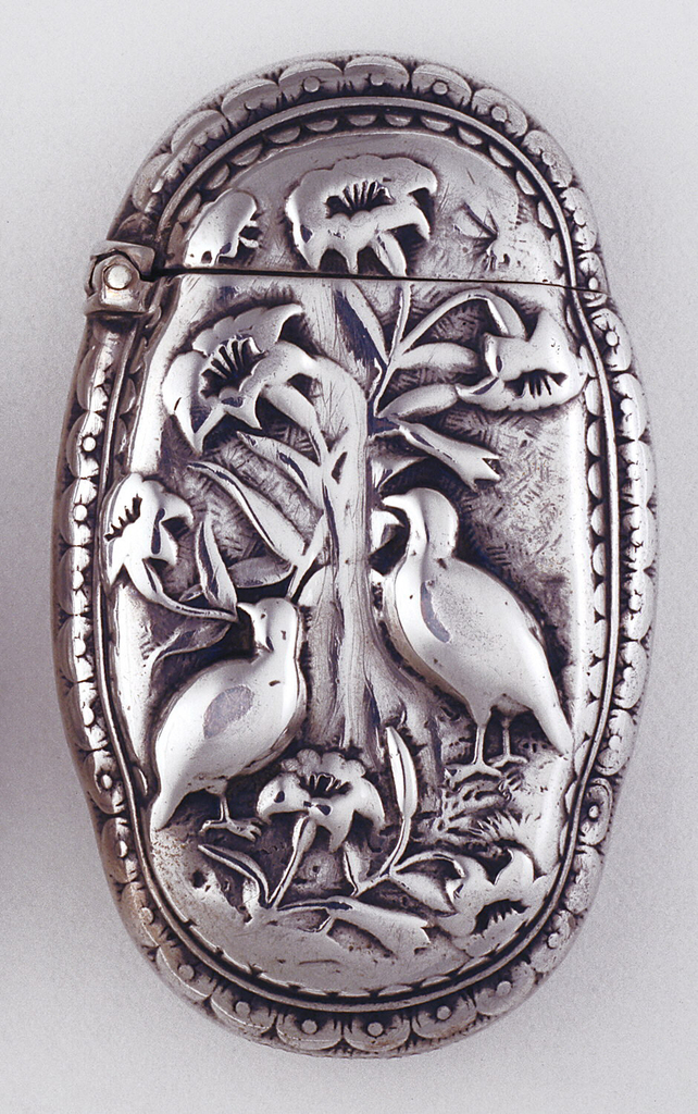 Oval, with upper and lower of left and right sides cinched slightly, featuring raised decoration of a pair of quails and lily flowers, all framed by double band of petal-like ornament. Reverse features rooster and hen among floral decoration. Lid hinged on side. Striker incised on bottom.