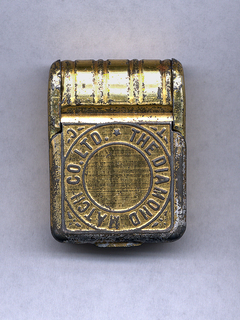 """Rectangular, upper part curved with bands that run from front to back, cover opens on front, thumb catch at bottom, cover inscribed in a circle """"The Diamond Match Co. Ltd."""", """"T"""" and """"C"""" inscribed on corners outside of circle. Striker on bottom beneath thumb catch."""