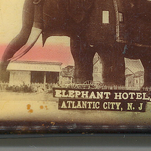 "Rectangular, curved top and bottom, image text reads horizontally, featuring sepia-toned, hand colored photographic image of structure that resembles an elephant with windows, and tower on its back, inscribed ""Elephant Hotel, Atlantic City, N.J."" Reverse features photographic image of people strolling on paths in garden-like setting, large building with veranda, canopied windows on ground floor, mansard roof and American flags above, sign in front inscribed ""Hotel Shelburne, Atlantic City, N.J."" Lid hinged on long side. Striker on opposite bottom."