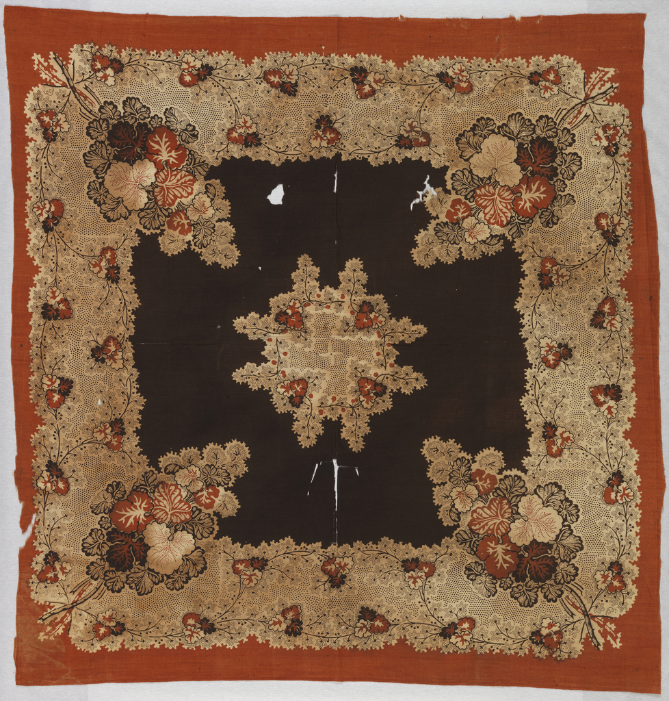 Fabric for a handkerchief in brown and orange with a central floral medallion and a wide border in a vine and flower design. Border is orange and center is dark brown.