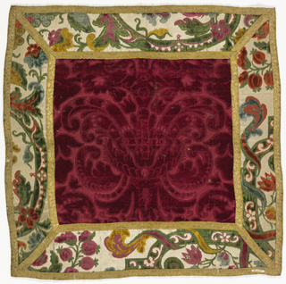 Corporal has a center of red cut and uncut velvet in a large-scale symmetrical foliate design with a border of polychrome cut and uncut velvet on a white satin ground in a floral design. Trimmed with gold ribbon and backed with red wool.