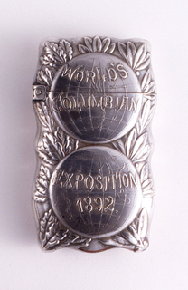 """Oblong, rounded corners, curved sides, featuring raised decoration of 2 stacked globes, the top inscribed """"World's Columbian"""", the bottom inscribed """"Exposition 1892"""", both set against foliate backdrop of oak and laurel leaves. Reverse features oblong wreath of oak and laurel leaves on unadorned background. Lid hinged on side. Striker recessed in groove on bottom."""