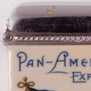 """Rectangular, featuring printed decoration of a red, white and blue banner, one large star in upper left, blue corner; golden eagle set against white ground on diagonal central band, eagle situated above green banner that is inscribed """"Pan 1901""""; 4 small stars on lower right, red corner. """"Pan-American Exposition 1901"""" inscribed in blue above flag; """"Buffalo, N.Y., U.S.A."""" inscribed in blue below. Reverse features representations of North and South America in the forms of fin-de siecle style women draped in flowing scarfs, their hands clasped at the isthumus, where the 2 continents meet. Inscribed in black on box side is """"Made by the Whitehead & Hoag Co., Newark, , N.J.""""; inscribed on opposite side: """"Designs Copyrighted by Pan-American Exposition Co."""" Lid hinged on side. Striker on bottom."""