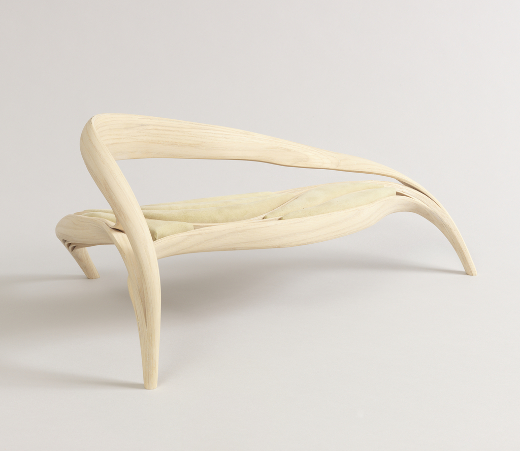 Organic curves of ash wood rising from three narrow feet to form a back and seat, the latter of undulating form, with velours upholstered channels following the forms of the chair.