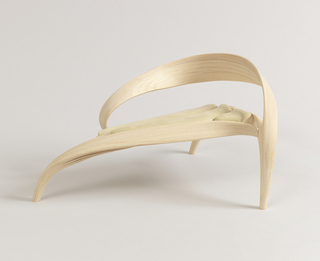 Long form of curved ash wood elements comprising sinuous, ribbon-like back, elongated triangular seat decending into three tapering legs; seat with three curved inserts covered in light green velour.