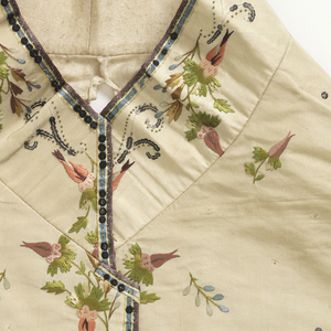 Gentleman's waistcoat with straight hem and standing collar. Cream silk embroidered foundation showing pattern of small scattered flowers and sequins. Embroidered around the collar and straight pockets with flowers carried out in satin stitch, and sequins. Appliquéd with sequins and printed satin weave silk medallions. The medallion below the left pocket is of Diana disarming Cupid, the one below the right pocket is of Venus playing with Cupid. Silk-covered buttons embroidered with flowers.