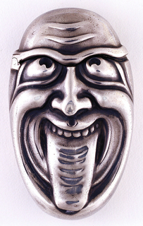 Oval, in the form of a face with eyes looking upward and crossed, furrowed brow, wide open grin, and tongue extended out and down over chin. No ornament on reverse. Area from top of head down to continuous eye brow line is lid, hinged on upper left side. Ridged tongue likely intended as striker.