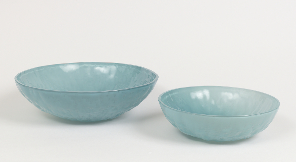Each bowl a transluscent acqua blue hemispherical body, one smaller than the other, their surfaces showing the texture and irregularities of the stone production molds.