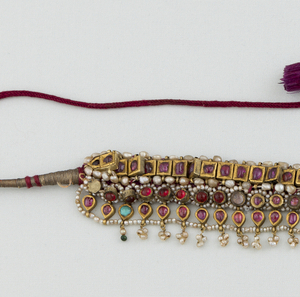 three bands of rubies set in various shapes of gold mounts with pearls in between and centered by a ruby-set florette