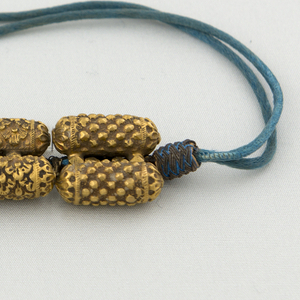 cylindrical long beads of textured gold, each bead a different pattern with small beads on a blue-green silk cord
