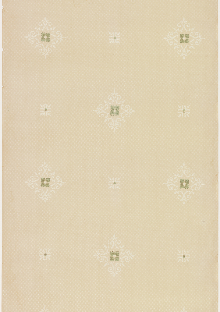 Rows of alternating diamond shaped medallions containing green quatrefoils, and smaller square medallions, both composed of foliate scrollwork. Medallions are printed over an allover pattern of small white dots. Pattern is printed in green, brown and white on khaki ground.