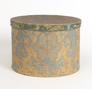 a) Oval box covered on one side with wallpaper printed in blue with orange outlines, in a bisymmetrical design; on back, a woman's hat printed in black, with legend: Wm Campbell's New York Patent Mould Band Box Manufactory, No. 297 Pearl Street, N.Y.; b) Cover, with matching wallpaper on top, and vari-colored paper on edge.