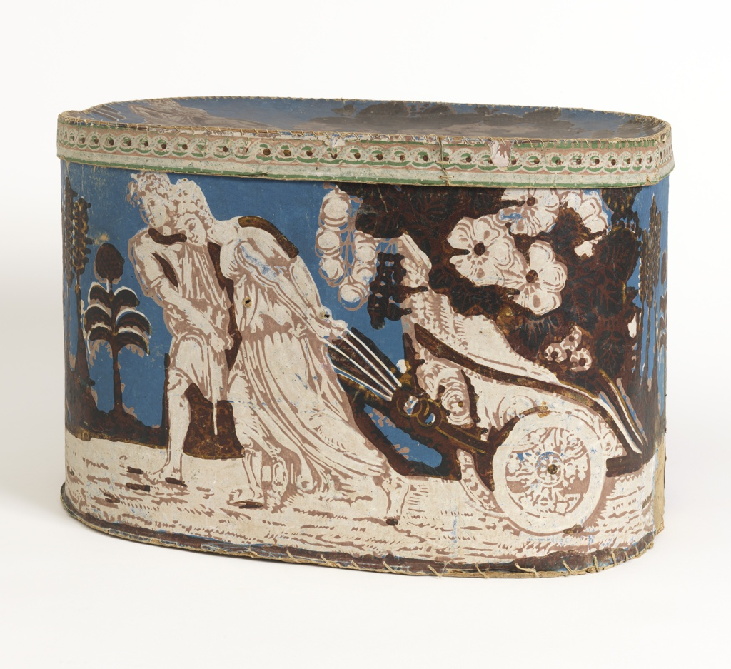 """Cardboard bandbox and lid covered with wallpaper with design called """"Quadriga Filled with Flowers."""" Deep blue background, classically draped man and woman pulling chariot (quadriga) filled with flowers, white pink, deep red and yellow. Rim of lid, white and deep red redorte or link chain, block print."""