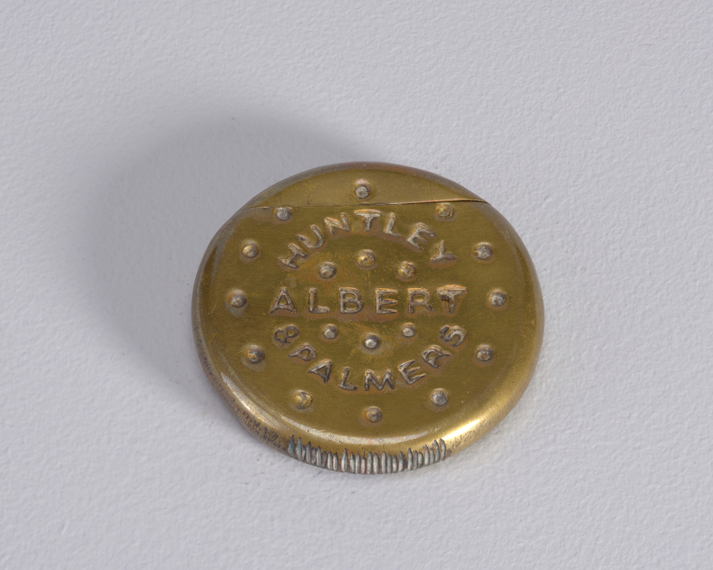 """Circular, in the form of a biscuit, with small, dot-like, simulated perforations on front surface, inscribed """"Huntley & Palmers,"""" """"Albert."""" On reverse are small, vertical and horizontal, dash-like, simulated perforations. Outer circumference of box displays irregular, scratch-like marks in surface. Lid, or upper portion of biscuit, hinged on back. Striker on bottom edge."""