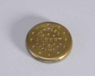 "Circular, in the form of a biscuit, with small, dot-like, simulated perforations on front surface, inscribed ""Huntley & Palmers,"" ""Albert."" On reverse are small, vertical and horizontal, dash-like, simulated perforations. Outer circumference of box displays irregular, scratch-like marks in surface. Lid, or upper portion of biscuit, hinged on back. Striker on bottom edge."