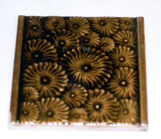 """Square, molded tile of white clay, the reverse is inscribed: """"J. & J.G. Low, Patent Art Tile, Works, Chelsea, Mass. U.S.A. Copyright 1881 by J. & JG Low"""" The impressed inscription is set within a double line frame; face of tile is decorated with an all over pattern of daisty-like flowers set between plain, horizontal bands. Glaze is a deep crackle brown."""