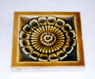 """Square, molded tile of white clay, reverse is embossed with an inscription framed in three concentric circles: J. & J.G. Low, Patent Art Tile Works, Chelsea Mass"""" Face is decorated with a stylized rosette set in a plain, narrow frame; crackle glaze is mustard yellow."""