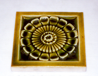 """Square molded tile made of white clay. Tile back has design of raised concentric circles framing inscription: """"J. & J.G. Low, Patent Art Tile Works, Chelsea Mass. U.S.A., copyright 1881 by J. & J.G. Low"""". Face of tile has central rosette framed by plain narrow border. Tile is painted mustard-green crackle glaze."""
