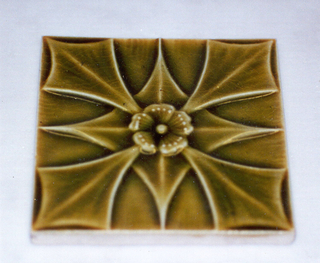 """Square molded tile made of white clay; reverse has relief design of three concentric circles which framing inscription: """"J. & J.G. Low, Patent Art Tile Works, Chelsea Mass. U.S.A., copyright 1881 by J. & J.G. Low"""". Face of tile decorated with stylized flower with four large blade-shaped leaves, four pointed leaves, dogwood blossom center, and pea green crackle glaze."""