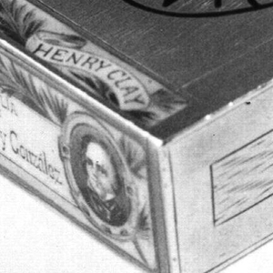 "Rectangular, in the form of a cigar box, with simulated, incised wood grain, inscribed in black enamel on top, resembling oval stamp, ""La Flor de Henry Clay, Julianalvz., Habana"". On left in polychrome enamel, with portrait medallion and foliage, is simulated label that wraps from edge of top surface down over left side, inscribed ""Henry Clay - Regalia de Alvarez y González"". Lid on right side. Striker in recessed groove on lid."