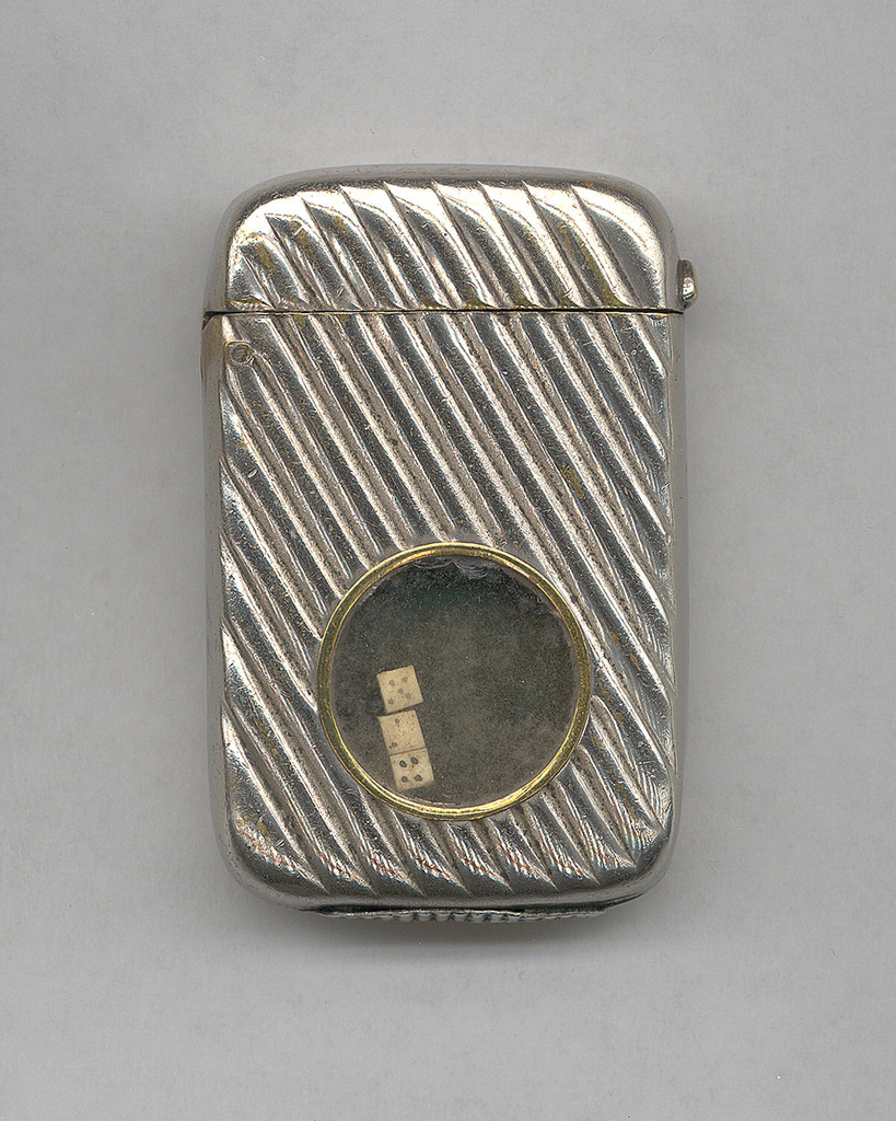 Rectangular, curved sides, rouned corners, featuring raised, diagonal bands all over; in recess at front, near bottom, is circular, glass covered compartment with brass edge and 3 small dice inside. Lid hinged on side, thumb catch opposite side. Striker on bottom.