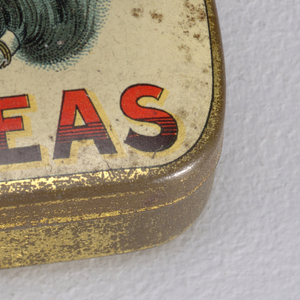 "Rectangular, rounded corners, with transfer printed decoration on lid, inscribed ""Tetley's Teas"" in large red and black type-face, highlighted in yellow, featuring central image of blue elephant's head with red kerchief, elephant holds at end of curled trunk box on a string, box inscribed ""Indian Ceylon,"" above box inscription reads ""Trade Mark,"" all on off-white ground, edges, sides and underside gold. Lid hinged at back. Striker on underside."