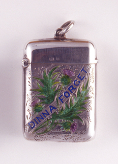 """Rectangular, with engraved thistles and foliage on body, enameled in pink and green.  A diagonally draped banner, inscribed """"DINNA FORGET"""" in blue enamel, bisects the decoration. No decoration on lid or reverse. Link attached to top of lid. Lid hinged on left. Striker on bottom."""