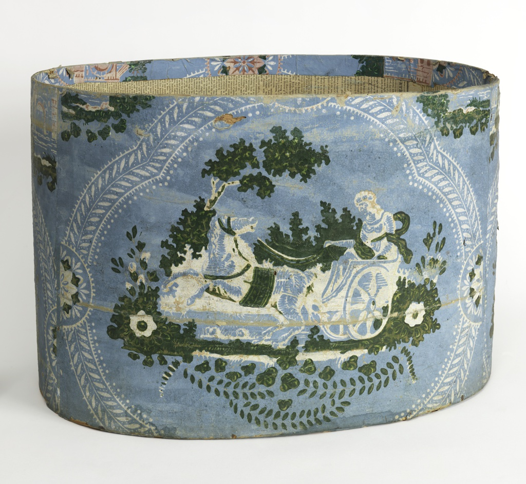 Blue field; medallion of woman driving a chariot, green and white, with small amount of pink; enframed in white conventional foliage scrolls. Inside of box lined with newpaper dated 1827.