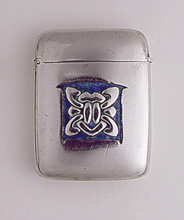 Rectangular, rounded sides and corners, featuring arts and crafts style decoration of a raised Celtic knot motif against a mottled blue/green enameled background in small, irregularly shaped, central reserve. Lid hinged on upper left side. Striker on bottom.