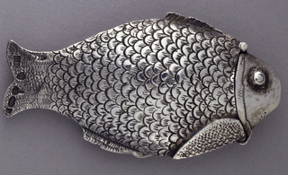 In the form of a fish, with incised scale-like decoration on body, finer incised decoration on small upper and lower fins as well as tail. Face plain except for saw-tooth, incised band that wraps from front to back, and applied, raised eyes. Face serves as lid, hinged at top with small hook catch underneath. Textured body likely intended to serve as striker.
