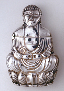 In the form of a Bodhisattva, draped in loose clothing, seated on a lotus flower and assuming the Lotus position for meditation, with arms resting on crossed legs, thumb and forefinger of each hand forming a circle in front; head and shoulders (lid) open to right. Striker on bottom.