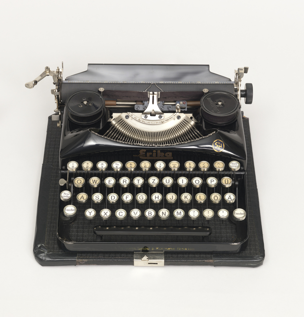 Typewriter (a) comprising mechanics set in black metal housing on flat leather-covered base; open keyboard; black ribbon. Black plastic keys with metal rims. Black leather-covered lid (b) with handle at front.