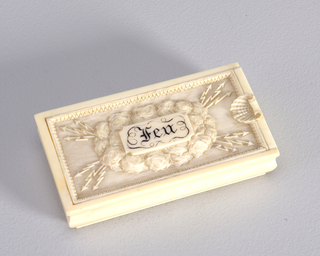 "Rectangular container, contoured sides, and slide-off lid with carved decoration, featuring central reserve inscribed ""Feu"" in black pigment, beneath which is a large cloud formation. Three lighting bolt-like arrows radiate outward from cloud mass at all four corners. Background has fine, engraved horizontal lines and all is framed by a serrated or leaf surround. Small, scalloped shell on lid at right serves as thumb catch. Surface of box bottom carved with fine cross-hatch marks for striker."