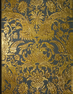 Imitation leather. Padded and embossed floral and foliate design with phoenix-like birds perched on acanthus leaf center motif. Background handpainted. Printed in bronze gold and blue gray.