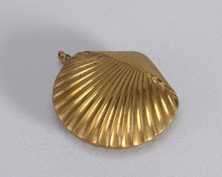 In the shape of a scallop shell, narrower end flips open, hinged on back. Link attached to side. Striker incised in back.