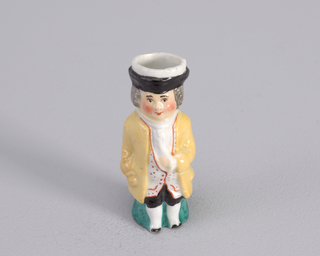 Figure of man in 18th c. costume with yellow coat, black short pants, long white waistcoat with red trim, white ruffled shirt, and black and white hat.