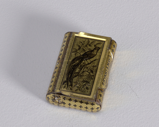 "Rectangular, curved sides, snuff-box style container, featuring cover of black printed decoration on gold ground of bird with long feathered tail perched on flowered branch; thumb catch to right inscribed ""Bryant & May's Wax Vetsas, Made in England"", small cross design on rest of body. Striker on reverse."