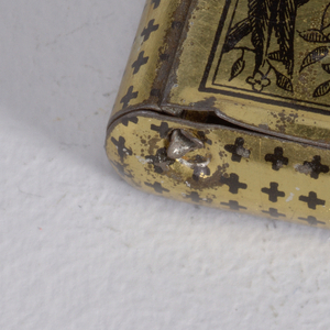 """Rectangular, curved sides, snuff-box style container, featuring cover of black printed decoration on gold ground of bird with long feathered tail perched on flowered branch; thumb catch to right inscribed """"Bryant & May's Wax Vetsas, Made in England"""", small cross design on rest of body. Striker on reverse."""